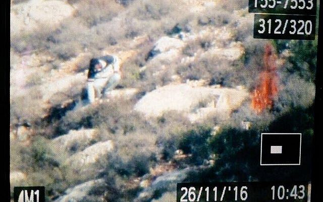 A photograph of a camera showing what appears to be a Palestinian man starting a fire in a field near Battir, outside of Bethlehem on November 26, 2016. (Parks Authority)