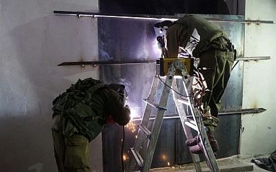 Israeli soldiers weld shut a workshop allegedly used to manufacture illegal guns in Yatta, outside Hebron, early in the morning on November 8, 2016. (IDF Spokesperson's Unit)