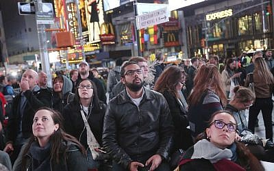 Pedestrians watch the election results on large screens in Times Square, New York, November 8, 2016. (AP Photo/Seth Wenig)