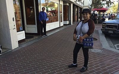 Alicia Ramirez, 67, hands out fliers to passersby on a busy street in a largely Latino area lined with money transfer businesses and shops selling elegant gowns for quinceanera celebrations in Santa Ana, California on Wednesday, Nov. 9, 2016. (AP Photo/Amy Taxin)