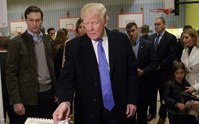 Republican presidential candidate Donald Trump is handed a sticker before casting his ballot at PS-59  in New York, November 8, 2016. (AP Photo/ Evan Vucci)