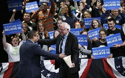 Then-Democratic presidential primary candidate Sen. Bernie Sanders, I-Vermont, is greeted by Rep. Keith Ellison, D-Minnesota, before speaking at a campaign rally, Monday, March 7, 2016, in Dearborn, Michigan. (AP Photo/Charlie Neibergall)