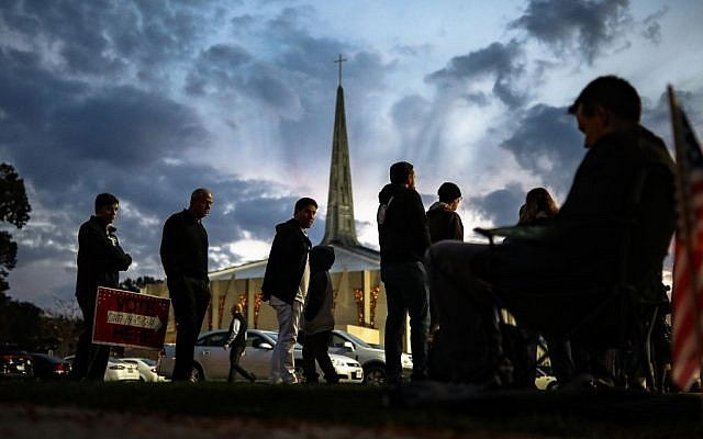 Adam Fohlen, his son Ari, center left, and others, wait in line outside a polling place at the Nativity School as a poll watcher sits nearby, Tuesday, Nov. 8, 2016, in Cincinnati. (AP Photo/John Minchillo)