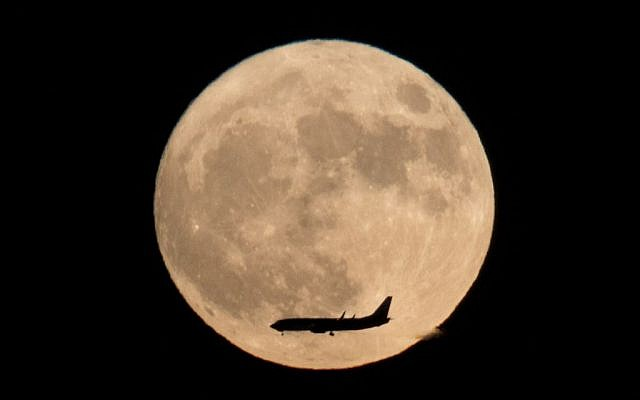 A jet plane flies across the supermoon,  brightest moon in almost 69 years, above Beijing, China, on November 14, 2016. (Ng Han Guan/AP Photo)