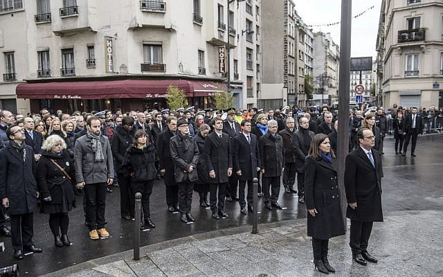 French President Francois Hollande and Paris Mayor Anne Hidalgo stand at attention after unveiling a commemorative plaque near the Petit Cambodge and Carillon cafes in Paris, France, on Sunday, November 13, 2016. (Christophe Petit Tesson/Pool Photo via AP)