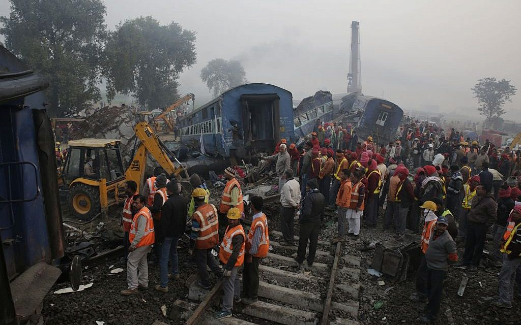 Rescuers work at the site after 14 coaches of an overnight passenger train rolled off the track near Pukhrayan village in Kanpur Dehat district of the northern Indian state of Uttar Pradesh, India, Monday, November 21, 2016. (AP/Rajesh Kumar Singh)