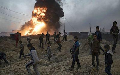 Children play next to a burning oil field in Qayara, south of Mosul, Iraq, Thursday, Nov. 3, 2016. (AP Photo/Felipe Dana)