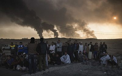Men are held by Iraqi national security agents, to be interrogated at a checkpoint, as oil fields burn in Qayara, south of Mosul, Iraq, Saturday, Nov. 5, 2016.  (AP Photo/Felipe Dana)