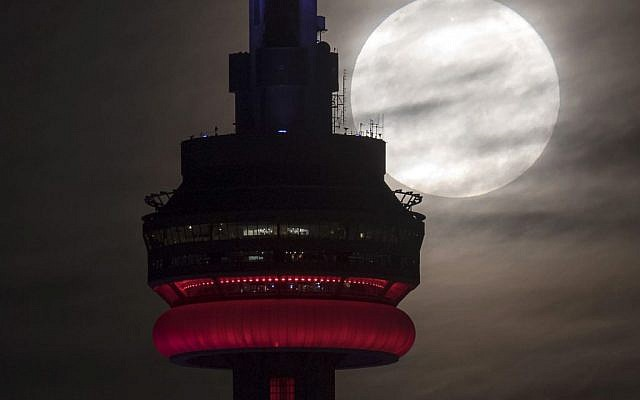 The brightest moon in almost 69 years sets behind the CN tower in Toronto on Monday, Nov. 14, 2016.  The phenomenon is known as the supermoon. (Frank Gunn/The Canadian Press via AP)