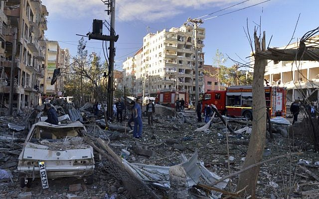 People watch the damage after an explosion in southeastern Turkish city of Diyarbakir, early Friday, Nov. 4, 2016. The cause of the explosion was not immediately known but Hurriyet newspaper said it may have been caused by a car bomb. (IHA via AP)