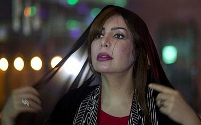 Saudi women's rights activist Souad al-Shammary puts on a head scarf in Jiddah, Saudi Arabia, Saturday, May 7, 2016. (AP Photo)