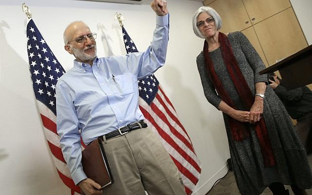 Alan Gross, freed from a Cuban prison earlier in the day, waves after concluding his remarks with his wife, Judy, at a news conference in Washington shortly after arriving in the United States, December 17, 2014. (Win McNamee/Getty Images)