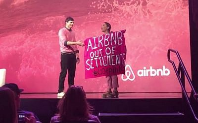 A protester against Airbnb's listing of West Bank settlement rentals during an interview with Ashton Kutcher at Airbnb Open in Los Angeles. November 19, 2016 (Screen capture: YouTube)