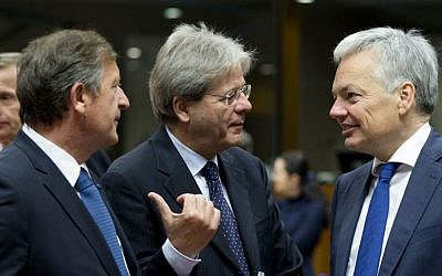 Italian Foreign Minister Paolo Gentiloni, center, speaks with Belgian Foreign Minister Didier Reynders, right, and Slovenian Foreign Minister Karl Erjavec, left, during a meeting of EU foreign ministers at the EU Council building in Brussels on Monday, Nov. 14, 2016. (AP Photo/Virginia Mayo)