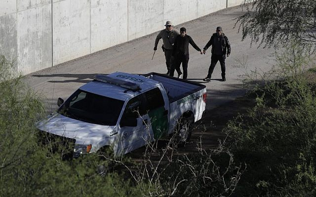 In this Wednesday, Nov. 16, 2016, photo, a US Customs and Border Patrol agent walks with suspected immigrants caught entering the country illegally along the Rio Grande in Hidalgo, Texas. (AP Photo/Eric Gay)