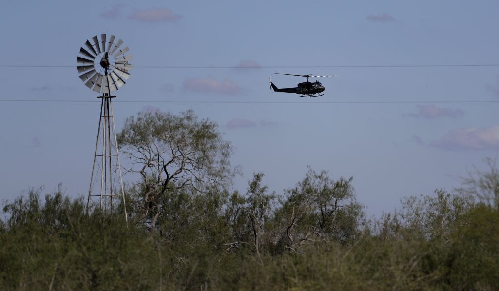In this Tuesday, Nov. 15, 2016, photo, a US Air and Marine Huey searches for immigrants who entered the county illegally on a ranch near Edinburg, Texas. (AP Photo/Eric Gay)