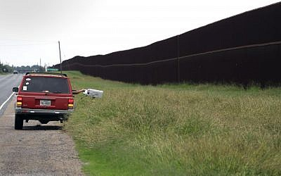 In this Monday, Nov. 14, 2016, photo, a carrier delivers mail along a section of border fence in Brownsville, Texas. The idea of a concrete wall spanning the entire 1,954-mile southwest frontier collides head-on with multiple realities, like a looping Rio Grande, fierce local resistance, and cost. (AP Photo/Eric Gay)