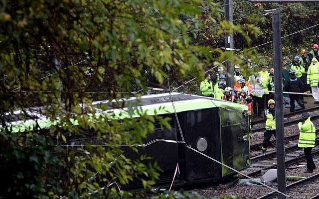 Emergency service workers attend the scene of a derailed tram in Croydon, south London, November 9, 2016. (Steve Parsons/PA via AP)