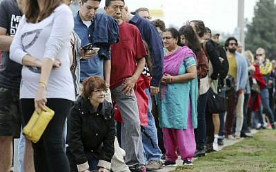 "In this Oct. 30, 2016 file photo, a woman kneels to take a ""back break"" while waiting in line at a weekend early voting polling place at the North Hollywood branch library in Los Angeles, California. (AP Photo/Reed Saxon, File)"