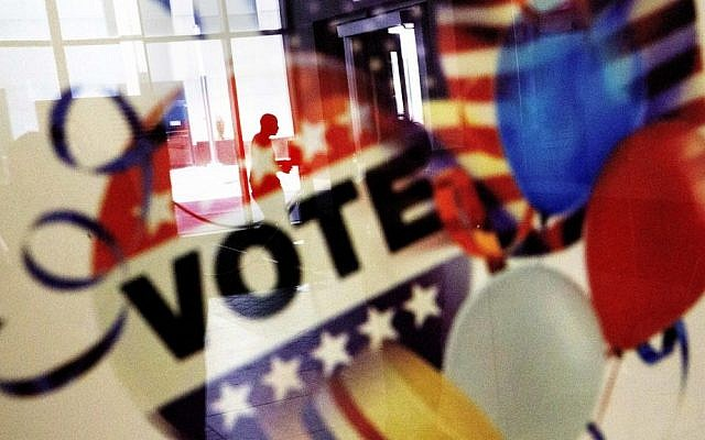 In this November 1, 2016, photo, a voter is reflected in the glass frame of a poster while leaving a polling site in Atlanta, during early voting ahead of the Nov. 8 election day. (AP Photo/David Goldman)