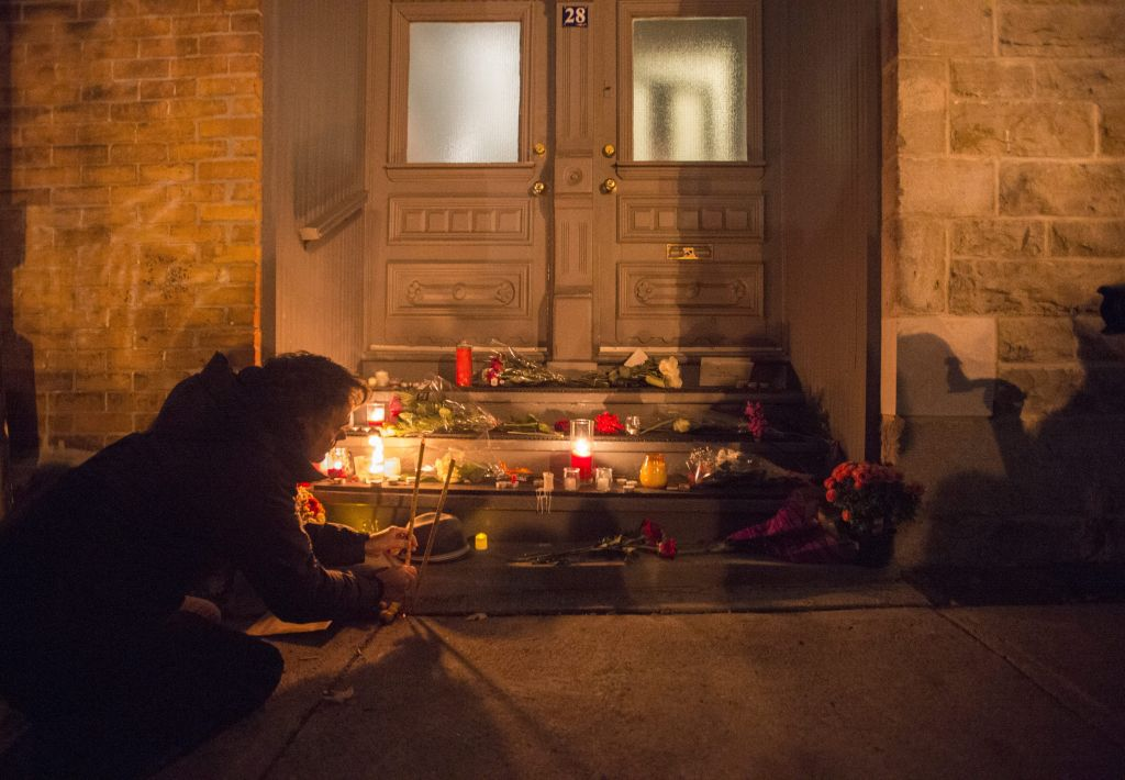 A man places candles in front of the home of singer and poet Leonard Cohen, Thursday, Nov. 10, 2016 in Montreal.  (Paul Chiasson/The Canadian Press via AP)