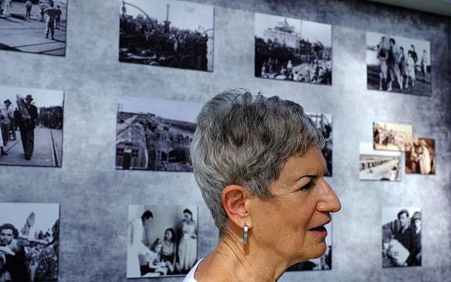 Nechema Friedman, 69, who was born at the hospital stands next to photos of that period in the British military camp, at the Cypriot military camp in capital Nicosia, on Wednesday, Nov. 9, 2016. (AP Photo/Petros Karadjias)