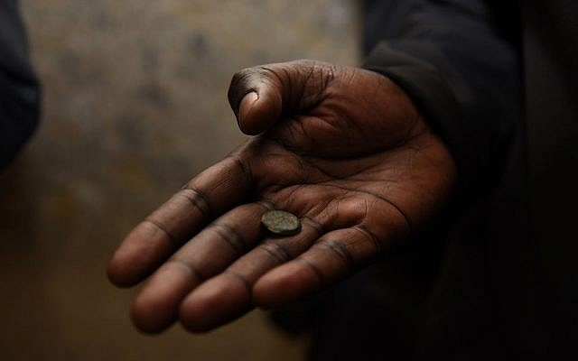 An African diplomat holding a 2,000-year-old Jewish coin in a tunnel near the Western Wall in Jerusalem. November 28, 2016 (Michel Rozili/City of David)