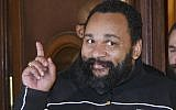 French comedian Dieudonne M'Bala M'Bala gesturing to the media as he leaves a Paris court house, February 4, 2015. (Michel Euler/AP Images/via JTA