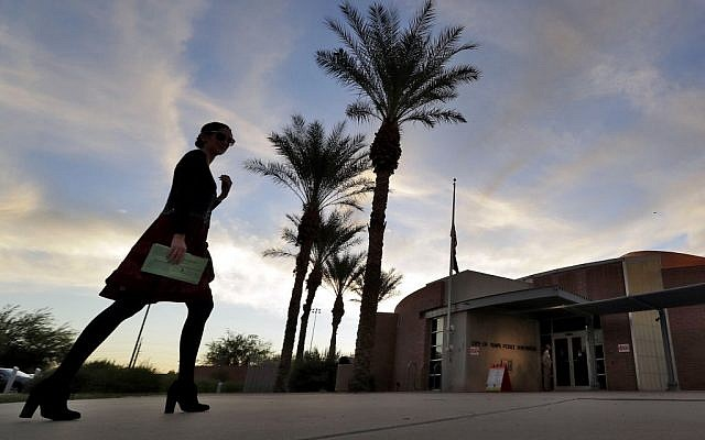 A voter carries in her mail in ballot to her polling station early, Tuesday, Nov. 8, 2016, in Tempe, Ariz. (AP Photo/Matt York)