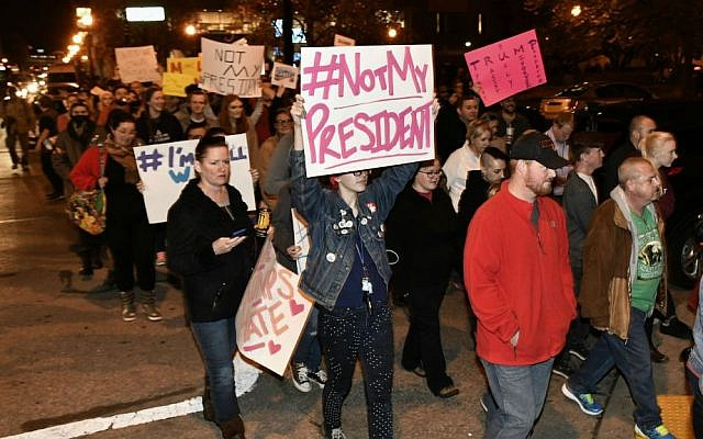 Protesters holds up signs in opposition of Donald Trump's presidential election victory as they march from Jefferson Square Park, Thursday, Nov. 10, 2016 in Louisville, Kentucky. (AP Photo/Timothy D. Easley)
