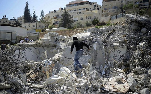 An illustrative photo of a Palestinian man climbing on rubble left after a house was demolished in the East Jerusalem neighborhood of Al-Tur on March 26, 2014, on the grounds that it was built without a construction permit. (Sliman Khader/Flash90)