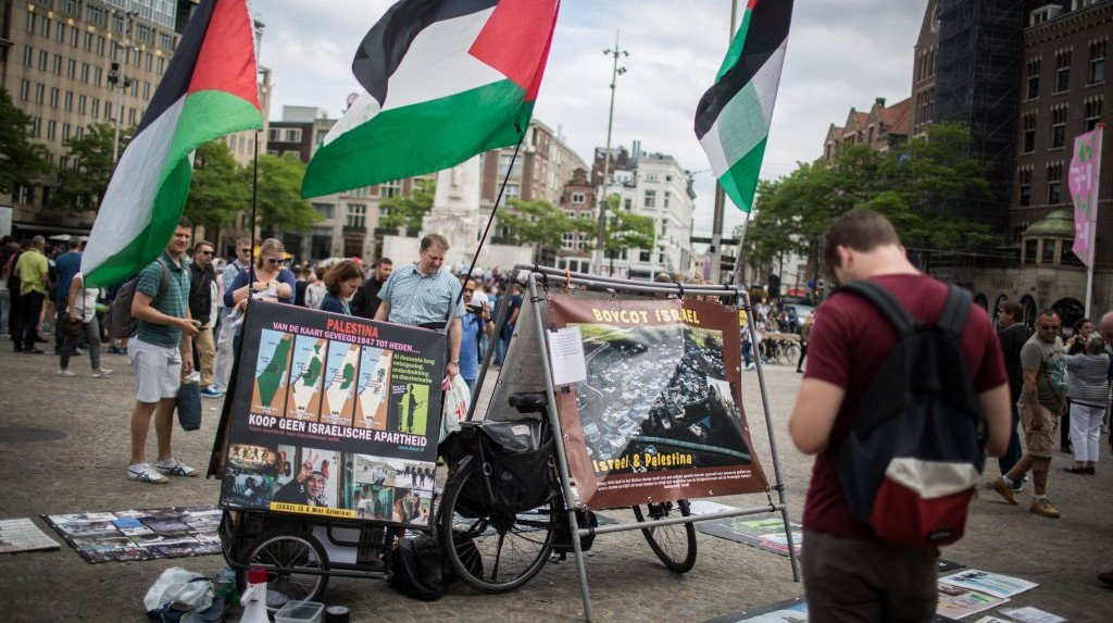 Israeli tourists look at a BDS stand with photos and Palestinian flags, calling to 'Free Palestine,' at Dam Square in central Amsterdam, the Netherlands, on June 24, 2016. (Hadas Parush/Flash90)