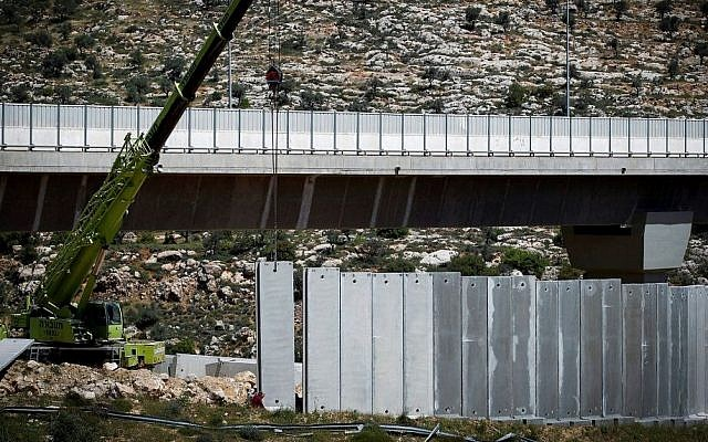 Israeli machines and workers build parts of the Israeli security barrier near the West Bank city of Beit Jala, outside Jerusalem, on April 17, 2016. (Wisam Hashlamoun/FLASH90)
