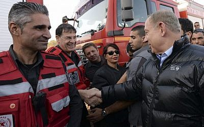 Prime Minister Benjamin Netanyahu speaks with Israeli firefighters during his visit at the fire command post in Zichron Yaakov, November 23, 2016. (Haim Zach / GPO)