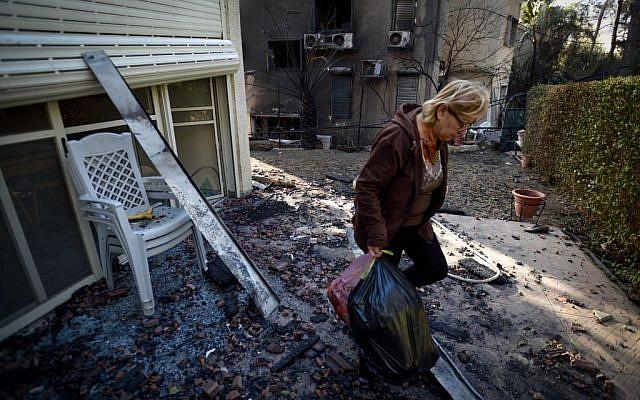 An Israeli woman carries some belongings from a burnt house, hit by a massive forest fire in the northern city of Haifa, Israel on November 25, 2016. (Gili Yaari/Flash90)