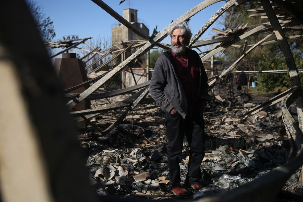 An Israeli artist stands in his studio, burned in an overnight fire in Beit Meir, outside of Jerusalem on November 25, 2016. (Hadas Parush/Flash90)