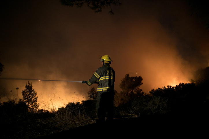 Firefighters try to extinguish a wildfire which broke out at the entrance to Nataf, outside of Jerusalem on November 25, 2016. (Yonatan Sindel/Flash90)