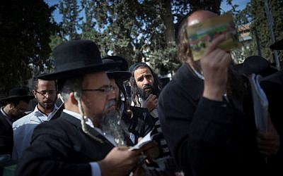 Ultra-Orthodox Jewish men gather to pray during a demonstration in support of Rabbi Eliezer Berland outside the Magistrate's court in Jerusalem where Berland was sentenced to prison for indecent acts and assault, on November 22, 2016. (Photo by Yonatan Sindel/ Flash90)