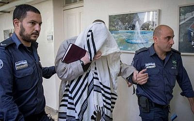 Rabbi Eliezer Berland covers himself with his talit (prayer shawl) at the Magistrate Court in Jerusalem where he was sentenced to prison for indecent acts and assault, on November 22, 2016. (Photo by Yonatan Sindel/ Flash90)