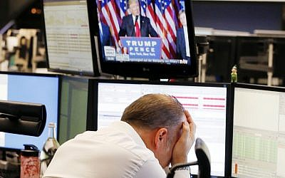 A broker reacts as President-elect Donald Trump shows up on a television screen at the stock market in Frankfurt, Germany, Wednesday, Nov. 9, 2016. (AP Photo/Michael Probst)