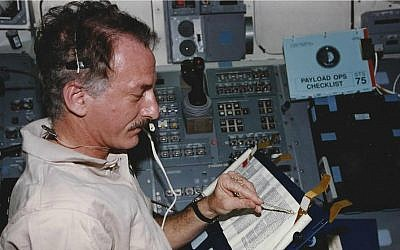 Jeffrey Hoffman reads from the Torah aboard the space shuttle Columbia during a 1996 mission. (Courtesy of Hoffman)