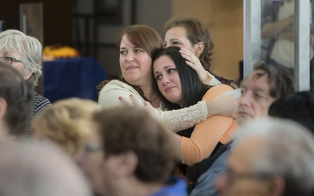 In this Oct. 30, 2016 photo Lorrie Zullo, left, and Jillian Eisman embrace at the Kupferberg Holocaust Center at Queensborough Community College in the Queens borough of New York. (Leo Correa/Queensborough Community College via AP)