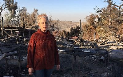 Rama Ben Zvi in front of the charred hull of her renowned country restaurant, Rama's Kitchen, in the village of Nataf, September 27, 2016 (Jessica Steinberg/Times of Israel)