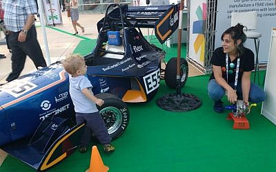 Lital Ben Shitrit, a Ben Gurion University student who worked on the BGR Ben Gurion Racing Team, demonstrates the use of carbon fiber to a young car enthusiast at the Israel Fuel Choices Initiative summit in Tel Aviv on November 3, 2016. (Melanie Lidman/Times of Israel)