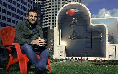"In this Friday, Nov. 11, 2016 photo, Mehdi Ghadyanloo, from Tehran, Iran, poses with his mural, ""Spaces of Hope,"" on the Rose Kennedy Greenway in Boston. (AP Photo/Bill Sikes)"