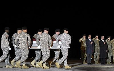 In this Monday, November 7, 2016 file photo, an Army carry team moves a transfer case containing the remains of Sgt. 1st Class Matthew C. Lewellen past Army Secretary Eric Fanning, fifth from right, Undersecretary of Defense for Intelligence Marcel Lettre, third from right, and Gen. Daniel B. Allyn, right, Army vice chief of staff, at Dover Air Force Base, Delaware.