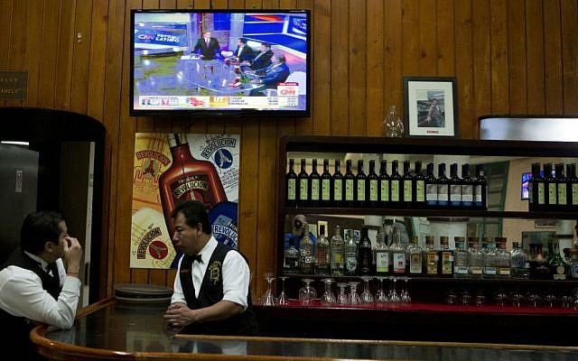 A waiter watches a local analysis of incoming US election results on a television in a traditional Mexican cantina in Mexico City, early Wednesday, Nov. 9, 2016. (AP Photo/Rebecca Blackwell)