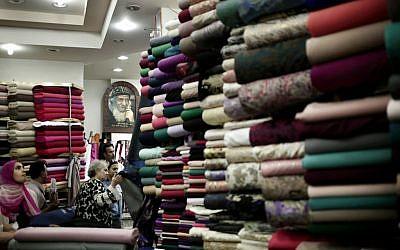 Egyptian women look at fabric inside a store in Wekalet El Balah, Cairo's famous fabric market, in Egypt, October 22, 2016. (AP Photo/Nariman El-Mofty)