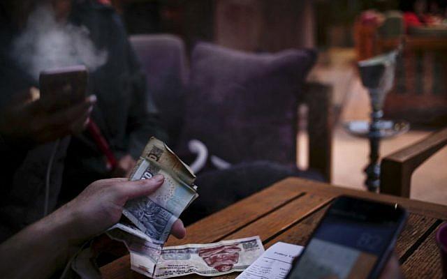 A man pays his bill as his friend smokes a waterpipe, or shisha, at a cafe in Cairo, Egypt, October 22, 2016. (AP Photo/Nariman El-Mofty)