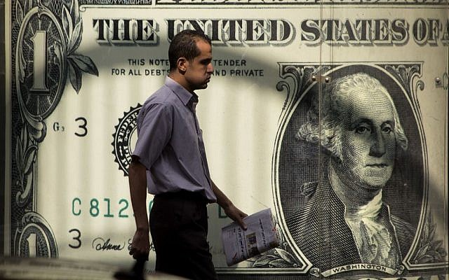 An Egyptian man walks past a poster showing a US dollar outside an exchange office in Cairo, Egypt, November 3, 2016. (AP Photo/Amr Nabil)